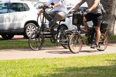 Montar a caballo de dos mangos una bicicleta eléctrica Foto de archivo libre de regalías