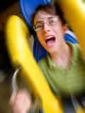 Montar a caballo de griterío del muchacho en una montaña rusa Imagen de archivo