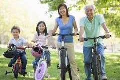 Montar a caballo de la bici de los abuelos con los nietos Foto de archivo libre de regalías