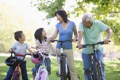 Montar a caballo de la bici de los abuelos con los nietos Imagen de archivo libre de regalías