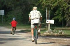 Montar a caballo de la bici de un más viejo hombre y del nieto Imagen de archivo libre de regalías