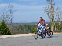 Montar a caballo de la bici del padre y de la hija Fotografía de archivo libre de regalías