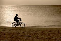 Montar a caballo de la bici en la playa Fotos de archivo