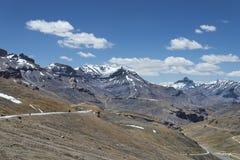 Montar a caballo de la bici por la carretera con curvas de la alta montaña fotografía de archivo