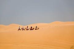 Montar a caballo de la caravana de los camellos en desierto fotos de archivo