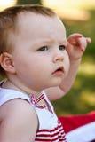 Montar a caballo de la chica joven en el carro rojo que se divierte en el parque para el cuarto de julio Imagen de archivo libre de regalías