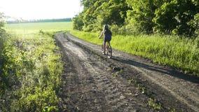 Montar a caballo de la chica joven en la bici en el camino rural en la puesta del sol almacen de metraje de vídeo
