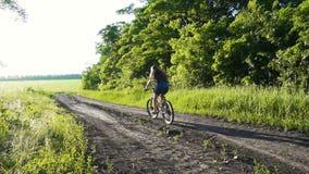 Montar a caballo de la chica joven en la bici en la carretera nacional en la puesta del sol almacen de metraje de vídeo