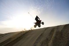 Montar a caballo de la duna en la puesta del sol Foto de archivo