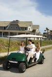 Montar a caballo de la familia en carro de golf. Fotos de archivo libres de regalías