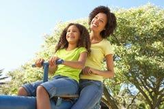 Montar a caballo de la madre y de la hija en el balancín en parque imagen de archivo
