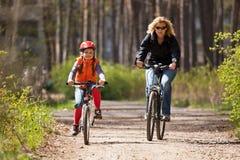 Montar a caballo de la madre y de la hija en las bicicletas Imagen de archivo libre de regalías