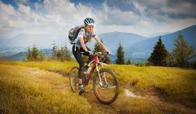 Montar a caballo de la montaña-bici de la mujer Fotos de archivo libres de regalías