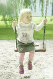 Montar a caballo de la muchacha de los años en el parque en un oscilación Imagenes de archivo