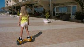 Montar a caballo de la muchacha del preescolar en el hoverboard en el parque imagen de archivo