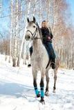 Montar a caballo de la muchacha en invierno soleado del caballo pálido Imagen de archivo libre de regalías