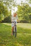Montar a caballo de la muchacha en la bici Foto de archivo