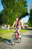 Montar a caballo de la muchacha en la bicicleta Foto de archivo libre de regalías