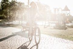 Montar a caballo de la muchacha en la bicicleta Imagen de archivo libre de regalías