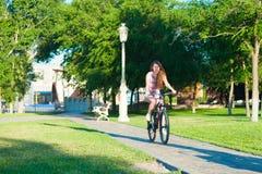 Montar a caballo de la muchacha en la bicicleta Imagen de archivo