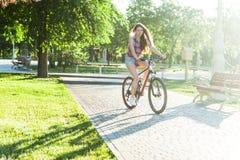 Montar a caballo de la muchacha en la bicicleta Fotos de archivo libres de regalías