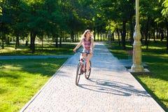 Montar a caballo de la muchacha en la bicicleta Fotografía de archivo libre de regalías