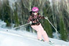 Montar a caballo de la muchacha en los esquís Imágenes de archivo libres de regalías