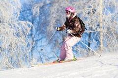 Montar a caballo de la muchacha en los esquís Foto de archivo