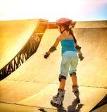 Montar a caballo de la muchacha en pcteres de ruedas en skatepark Hecho excursionismo en fondo Imagen de archivo libre de regalías