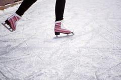 Montar a caballo de la muchacha en una pista de hielo Hielo y patines Los pies del hombre en patines imagen de archivo