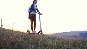 Montar a caballo de la muchacha en la vespa eléctrica en una cuesta de montaña en la puesta del sol, MES lento almacen de video
