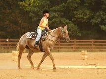Montar a caballo de la muchacha occidental Foto de archivo