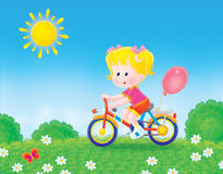 Montar a caballo de la muchacha su bicicleta en la hierba Fotos de archivo