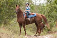 Montar a caballo de la muchacha su caballo Fotografía de archivo