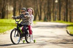 Montar a caballo de la muchacha y del muchacho en la bicicleta Foto de archivo