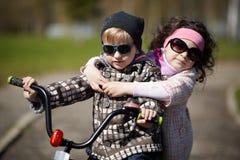 Montar a caballo de la muchacha y del muchacho en la bicicleta Imagenes de archivo