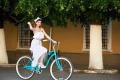 Montar a caballo de la mujer en la bicicleta en ciudad en los árboles del fondo, paredes Foto de archivo