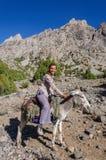 Montar a caballo de la mujer en burro en la montaña Fotografía de archivo