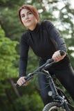 Montar a caballo de la mujer en la bici Imágenes de archivo libres de regalías