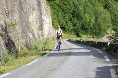 Montar a caballo de la mujer en la bicicleta Imagen de archivo libre de regalías