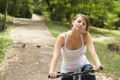Montar a caballo de la mujer joven con la bici Imagen de archivo