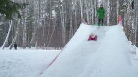 Montar a caballo de la niña de la cabeza de diapositiva grande del hielo abajo metrajes