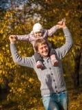 Montar a caballo de la niña en cuello de los papás en el parque del otoño Foto de archivo libre de regalías
