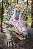 Montar a caballo de la niña en dinosaurio del Ankylosaurus Foto de archivo