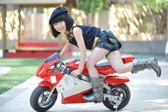 Montar a caballo de la niña en la motocicleta Fotografía de archivo libre de regalías
