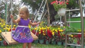 Montar a caballo de la niña en un oscilación de la cuerda en un jardín de flores almacen de metraje de vídeo