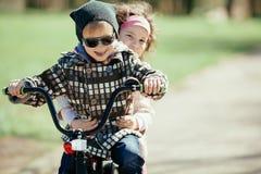 Montar a caballo de la niña y del muchacho en la bicicleta junto Imagen de archivo