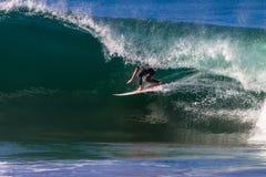 Montar a caballo de la persona que practica surf dentro de la onda hueco Foto de archivo
