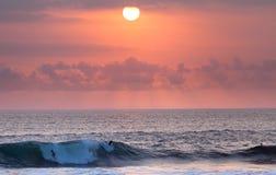 Montar a caballo de la persona que practica surf en la puesta del sol en ola oceánica Fotos de archivo libres de regalías