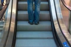 Montar a caballo de la zapatilla de deporte del desgaste de la muchacha en una escalera móvil pies que se colocan en la escalera  Fotos de archivo